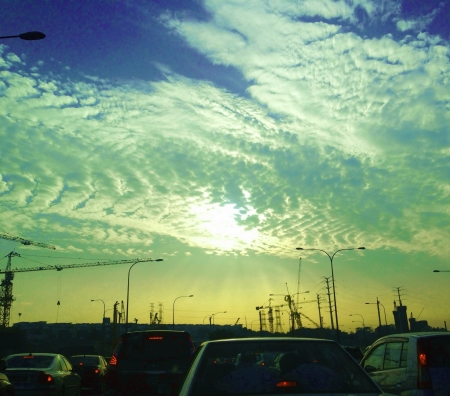 penetrating: Sun rays penetrating the clouds in the early morning during a massive traffic jam  Stock Photo