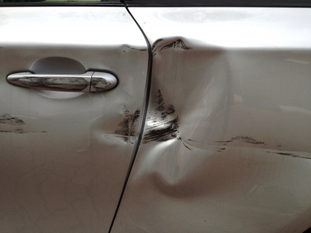 dent: Car door and paint damaged by a collision  Stock Photo
