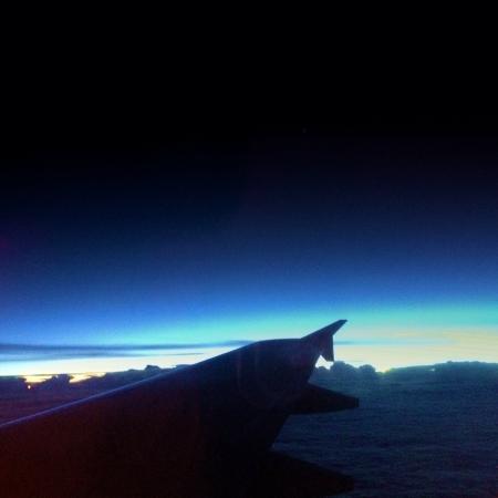 View from an aircraft midflight at sunset.