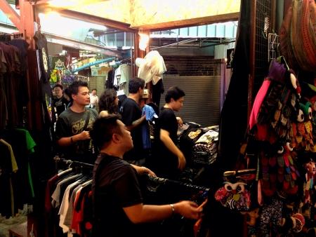 Customers shop in a packed garment shop in Jatujak Market Bangkok Thailand  Stock Photo