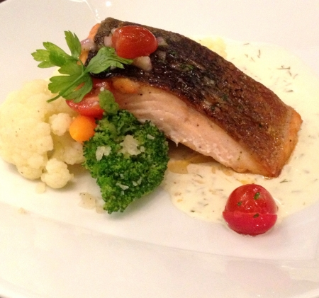 A gourmet dish of pan seared salmon with white sauce and garnishing