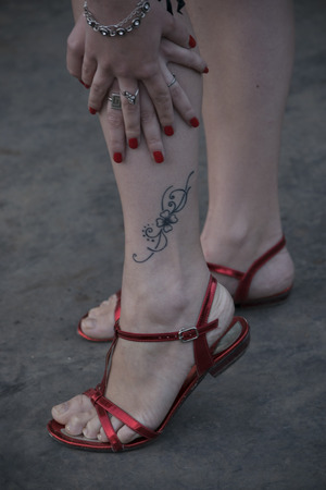 noticeable: female feet in red sandals with a tattoo