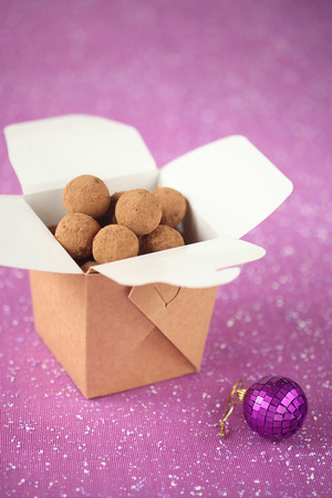 brown box: Chocolate Truffles in a brown box, with a Christmas ball and on a purple background