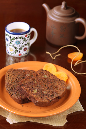 Two pieces of Chocolate Ginger Cake with dried apricots, on a brown plate  photo