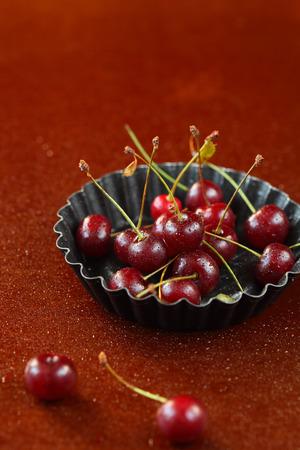 fondo cafe: Cerezas frescas con gotas de agua sobre un fondo de color marr�n brillante