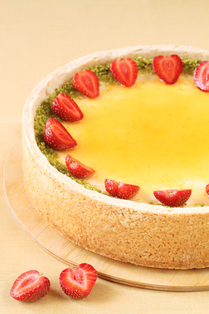 Vanilla Cheesecake with strawberries and pistachios, on a yellow background