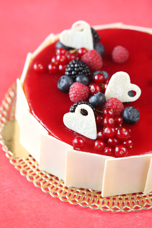 Summer Berries Cake with white chocolate hearts, on a red background  photo