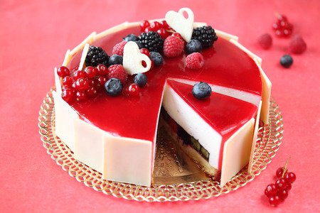 Summer Berries Cake with Coconut Mousse, on a red background  photo
