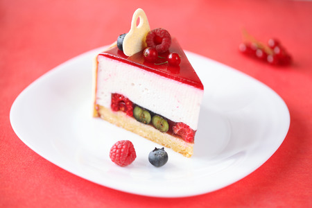 Piece of Summer Berries Cake with Coconut Mousse, on a white plate and red background  photo