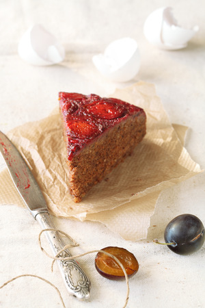 Piece of Upside-Down Plum Cake, on a baking paper, with silver knife, on a light background  photo