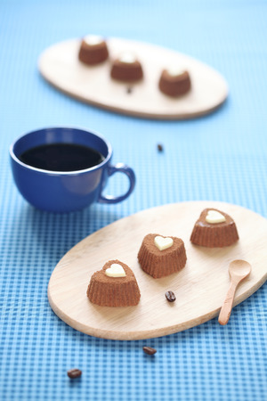 Chocolate Coffee Sweet Hearts on a wooden cutting board, with a cup of coffee, on a blue background  photo