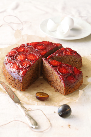 Upside-Down Plum Cake, on a baking paper, with silver knife, on a light background  photo