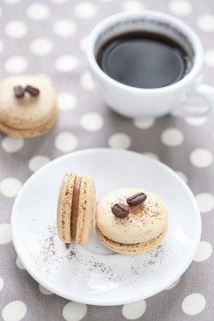 Coffee Macarons with a cup of coffee, on a grey polka dot background  photo