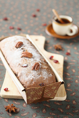 Honey and Spice Loaf Cake with candied fruit and pecans on a wooden cutting board, with a cup of coffee  photo
