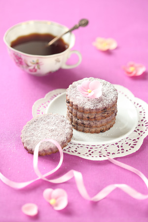 Blueberry cookies on a white plate, a cup of coffee, on a pink background  photo