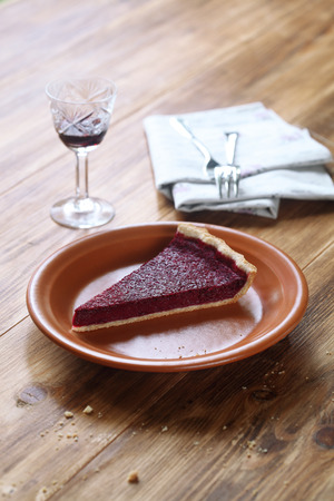 Piece of rustic berry tart on brown plate, on wooden table.