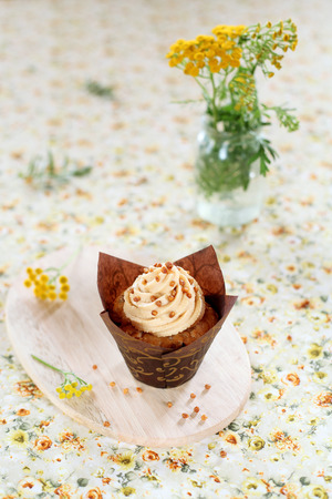 Peanut Butter Cupcake on wooden board, on yellow floral background.