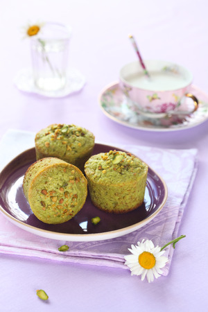 Pistachio Muffins on purple plate, on light purple background.
