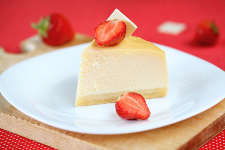 patisserie: Vanilla Cheesecake with Strawberries on white plate, on bright red background.