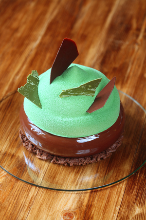 patisserie: Contemporary Multi Layered Mousse Cake with chocolate and matcha green tea covered with chocolate glaze and green velvet spray, on wooden background. Stock Photo