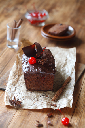 Chocolate Cherry Fruit Cake Loaf with Nuts, on wooden table.