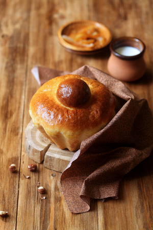 French Brioche Bun on wooden board, on wooden background. Stock Photo