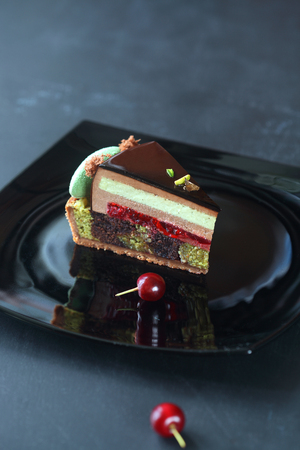 Piece of Contemporary Chocolate, Cherry and Pistachio Layered Mousse Cake, on black plate, on dark background. Stock Photo