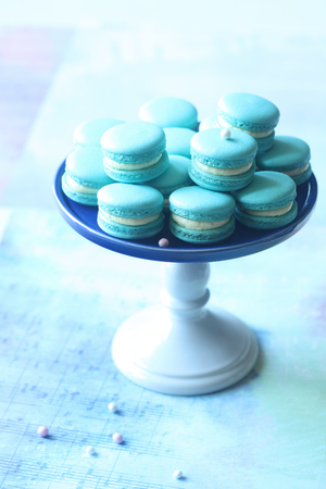 Blue Macarons with Cream Cheese and Blueberry Filling on a little cake stand, on light blue background. Stock Photo
