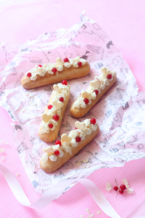 Eclairs with Vanilla Pastry Cream and Cream Cheese Filling, decorated with red currants and white chocolate hearts, on light pink background.