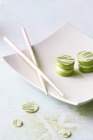 Upside Down Matcha Yuzu Macarons on white square plate, on light background.