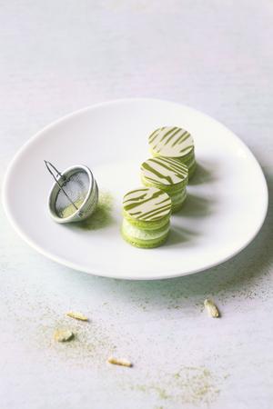 Upside Down Matcha Yuzu Macarons on white oval plate, on light background.