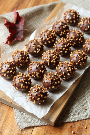 Chocolate balls - cakepops - on wooden board, with caramelized walnuts, on wooden background.