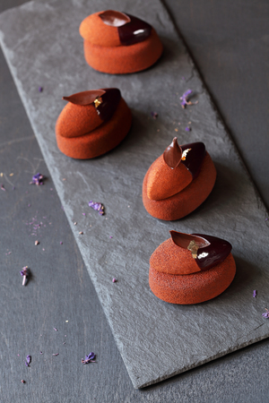 Contemporary Chocolate Violet Mini Cakes Mousse, on dark gray background.