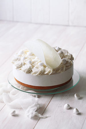 Angels Cake with Vanilla Souffle and Meringue Cookies, on white wooden table.