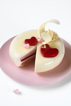 Contemporary Layered Yogurt Cake Decorated with Strawberry Jelly Hearts, on white background. Imagens
