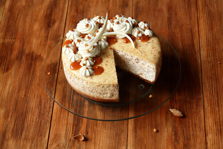 Almond Cheesecake decorated with caramel, on wooden table.