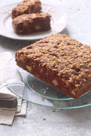 Vegan Square Chocolate Cake with Apples and Walnuts, on a plate, on a gray background. Stok Fotoğraf