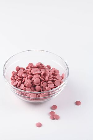 Ruby Chocolate Callets, in a transparent bowl, on white background. 写真素材