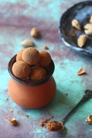 Homemade Chocolate truffles rolled in cocoa powder, in a little clay pot, on a vintage brown blue background. Banco de Imagens
