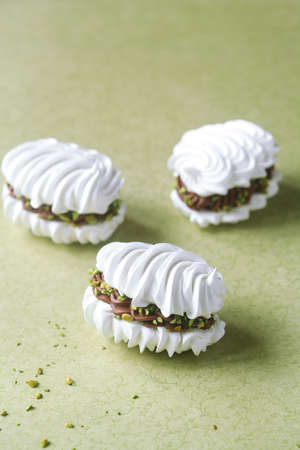French Vanilla Meringue Sandwich Cookies with Chocolate Ganache filling and Pistachios.