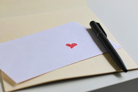 caes: Coraz�n rojo del amor en blanco del sobre Foto de archivo