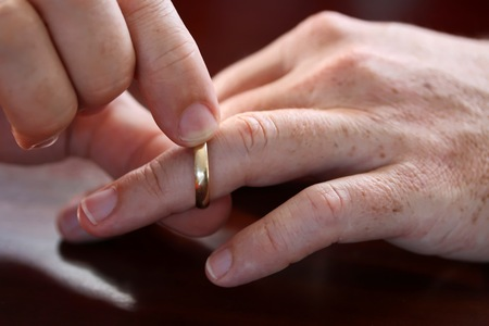 breaking off: Middle Aged Man Taking His Wedding Ring Off Stock Photo