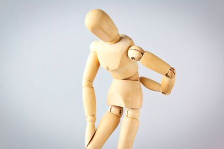 Wooden mannequin figure expressing back pain