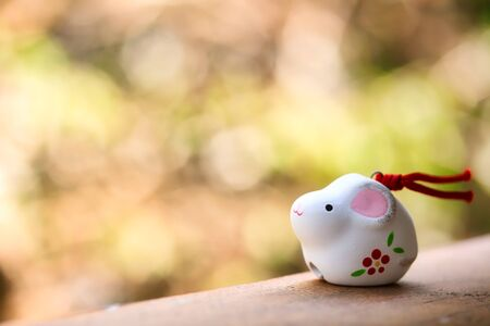 A cute looking Japanese good luck charm rat for celebrating year of the rat on green background.