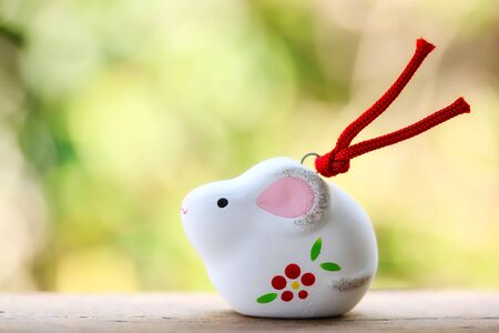 A cute looking Japanese good luck charm rat for celebrating year of the rat on green background. Stock fotó