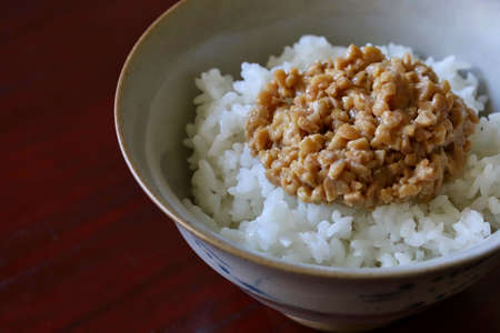A close up shot of some finely chopped fermented soybeans on freshly cooked white rice in a ceramic rice bowl. Imagens