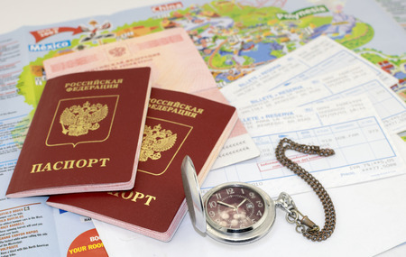 guidebook: Three russian passports, railway tickets and a pocket watch on the background of a map guidebook Stock Photo