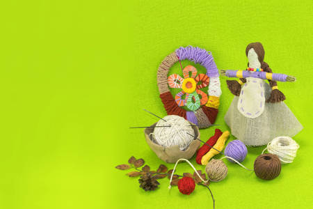 spokes: A horizontal green template with a folk handmade doll made of straw, linen, balls of wool and spokes with pine cone and herbarium Stock Photo
