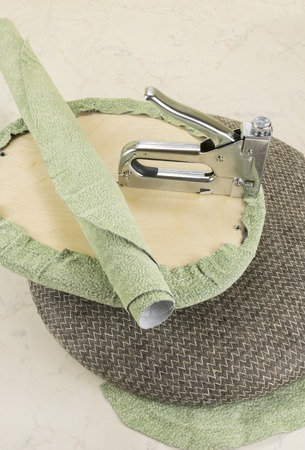soft textile: upholstering a padded part of soft chair by staple gun with textile covering