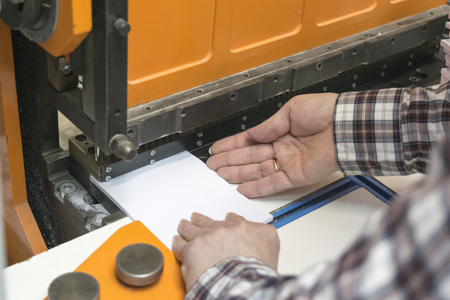cutting machine is: operator of guillotine machine are cutting papers Stock Photo
